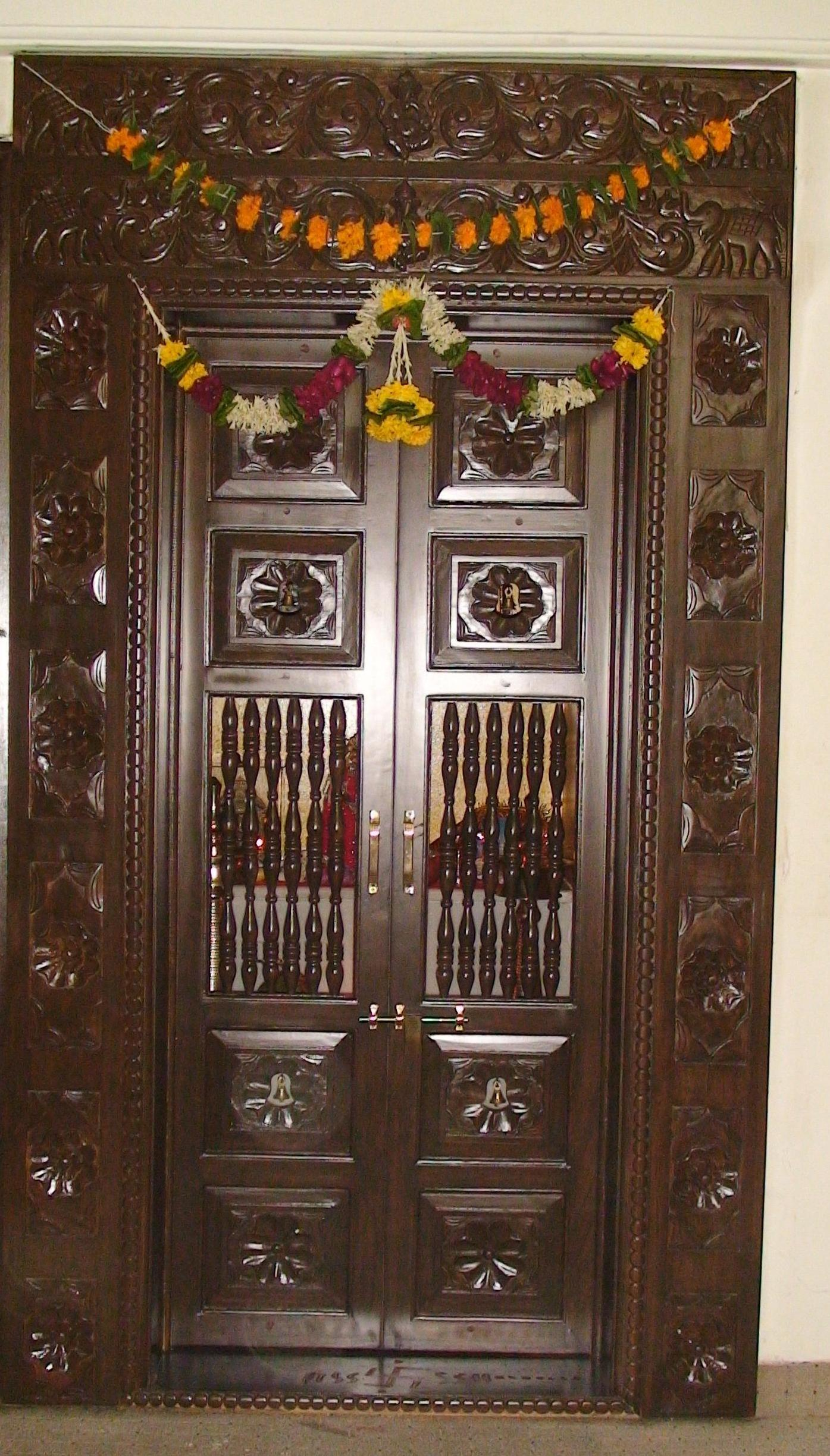 Wooden carved pooja room door design gharexpert for Room door design for home