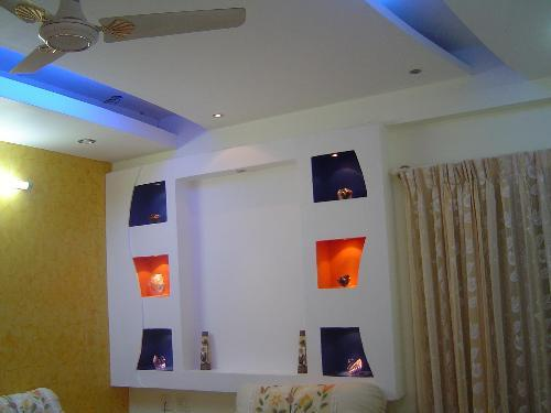 Living room false ceiling with colorful alcoves - GharExpert