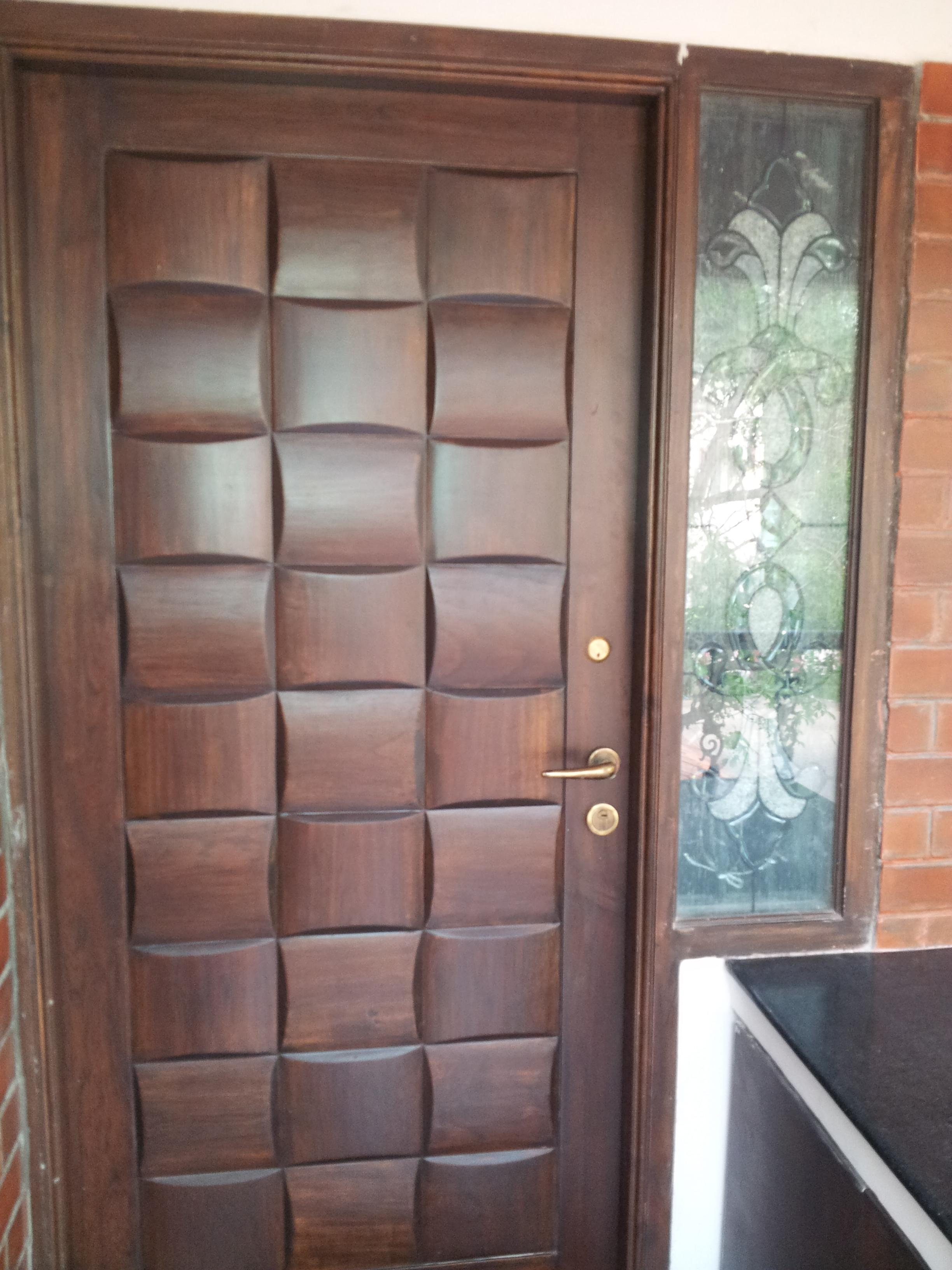 The main door is a Teak Paneled Door which gives the look of a weaved    Indian Modern Main Door Design